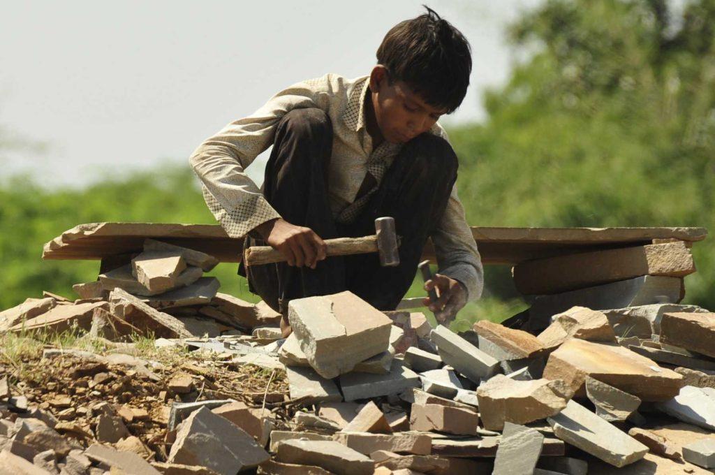 Junge beim Steineklopfen